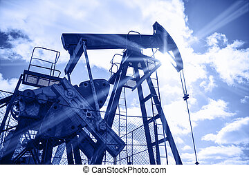 Oil rig. - Pump jack on a sky and sun background. Extraction...