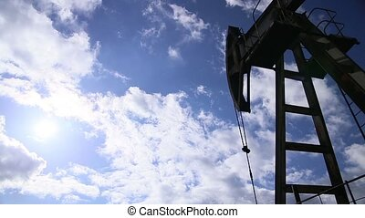 Oil rig pumping over sky. Loop footage.