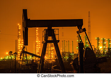 Oil rig silhouette at the background of refinery by night.