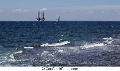 Oil rigs at sea, seen from the shore