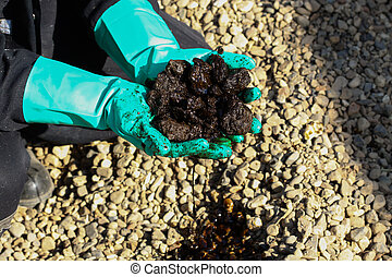 Oil sands development from an oil drilling district. The hand on the oil sands. Operator take oil sand s sample from mine.