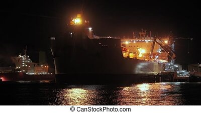 Large crude oil tanker vessel docked to the refinery dock at night in the port of Rotterdam