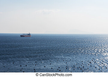 Oil tanker on the horizon in the sea near the city of Naples.