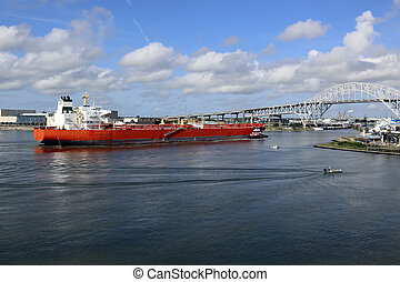 Large ship coming into port to deliver goods, Tug boat guiding the ship to keep it on path, Several small boats near by