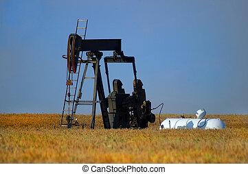 Oil Well in Field - An oil well in a field of wheat.