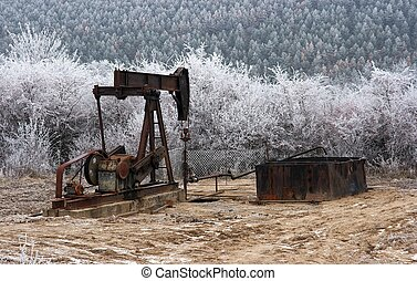 Old, rusty oil well on a winter landscape