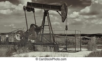Oil well on a landscape - Old rusty oil well on a field in...