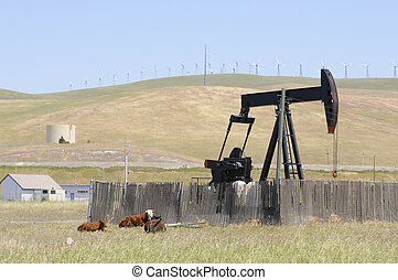 Oil well pump with wind generators in the background, showing old and new technology, or renewable and non renewable resources in northern California