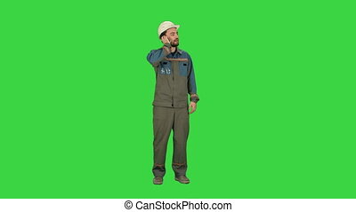 Oil Worker calling by phone during business break on a Green Screen, Chroma Key.
