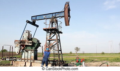 oil worker climbs up to the pump