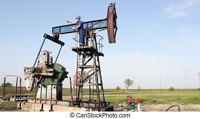 oil worker standing on pump jack