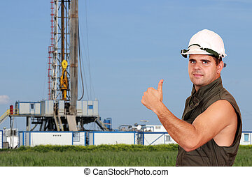 oil worker thumb up and land drilling rig
