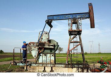 oil worker working on pump jack