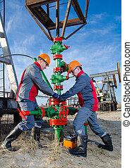 Oilfield workers - Workers in the oilfield repairing...
