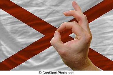 ok gesture in front of alabama us state flag