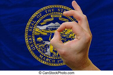 ok gesture in front of nebraska us state flag