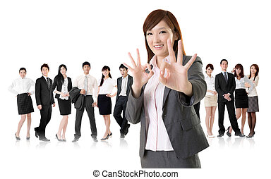 Smiling business executive woman of Asian give you an okay sign in front of her team isolated on white background.
