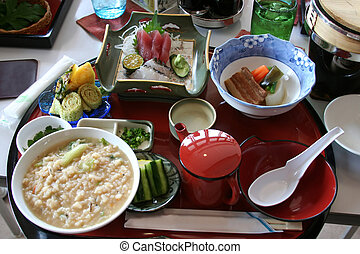 Tray of Okinawan food including porridge, tofu, sushi, daikon, pork, and seaweed.