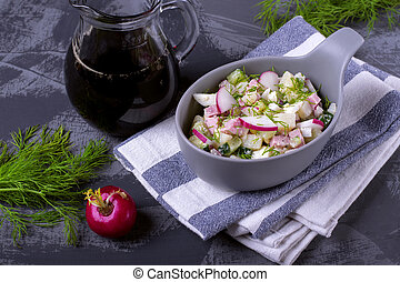 Okroshka soup with radish, sausage, cucumber, egg and potato in a ceramic bowl