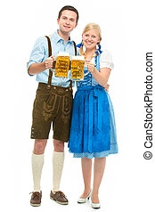oktoberfest - happy bavarian couple in dirndl with...