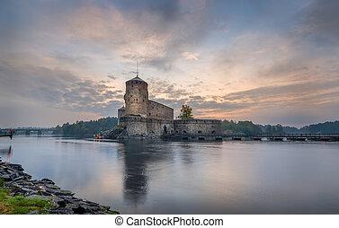 Olavinlinna fortress at sunrise. Early morning in Savonlinna, Finland.