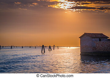 Old abandoned building of San Giacomo in Paludo island in Venice lagoon at sunset