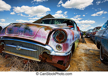 Old abandoned vintage cars rusting in a ghost town