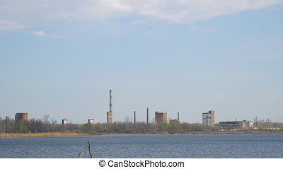Old Abandoned chemical factory with chimneys on the banks of...