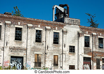 Old abandoned factory building - the brick wall with broken windows.
