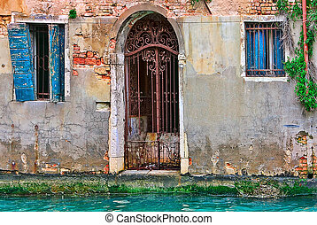 Old abandoned house on small canal in Venice.