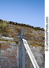Old abandoned house with a brick wall supported by wooden beams