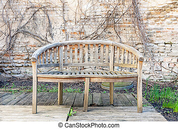Old abandoned outdoor bench in a background of weathered brick wall and dry plants