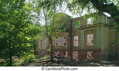 Old german mansion - abandoned and ruined historical building among green trees in Kaliningrad, Russia (formerly Koenigsberg) at sunny spring day. Static shot rendered in 4K