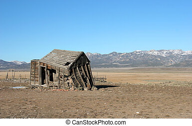 An old dilapidated shack sits in an empty field