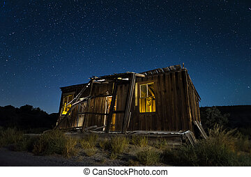 Old abandoned shack at night under a starry Nevada sky.