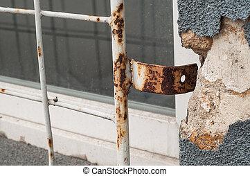 Old abandoned window with rusty broken iron bars