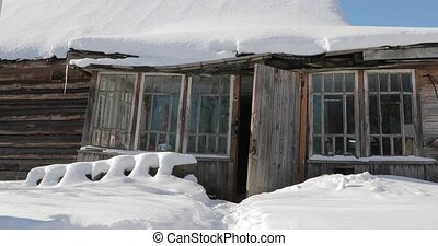 old abandoned wooden house under the snow