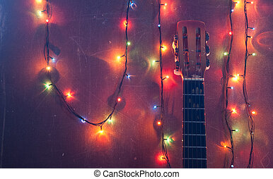 Old acoustic guitar with a garland on grunge background,
