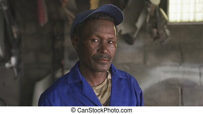 Old African handyman looking at camera