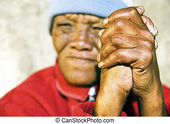 Old African woman with folded hands - focus on the weathered hands