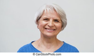 portrait of smiling senior woman over grey - old age and...