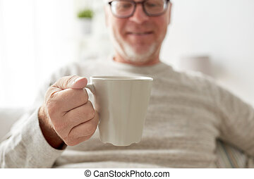 happy senior man with cup of tea or coffee at home