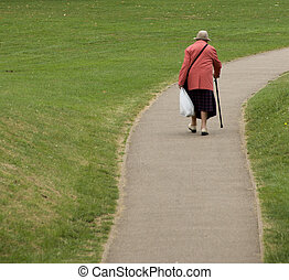 Old age - Elderly female with walking stick on deserted, ...