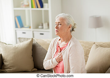 senior woman suffering from heartache at home