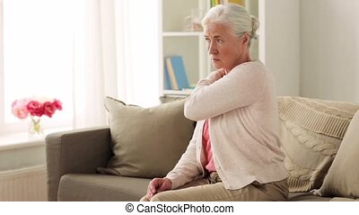 senior woman suffering from neck pain at home - old age,...