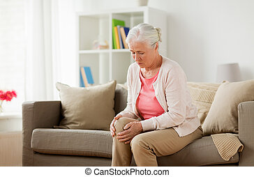 senior woman suffering from pain in leg at home - old age,...