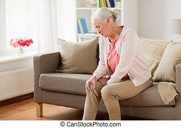 senior woman suffering from pain in leg at home - old age, ...