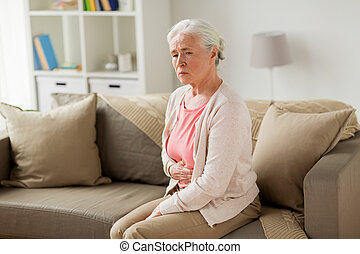 senior woman suffering from stomach ache at home - old age,...