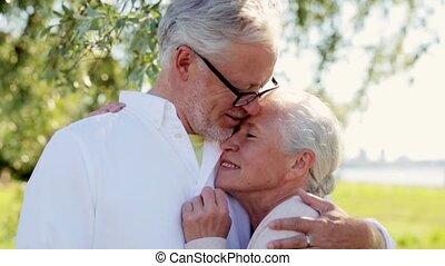 happy senior couple cuddling at summer park - old age, love...