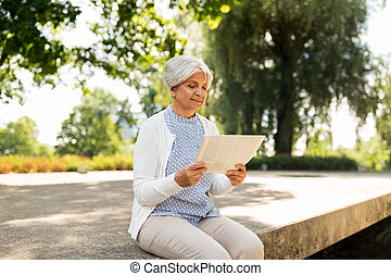 senior woman reading newspaper at summer park